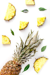 summer dessert with pineapples and leaves on white background top view