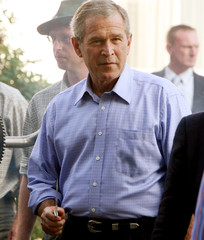 US President Bush holds a carving knife as he carves a roasted wild pig at a barbecue in Trinwillershagen