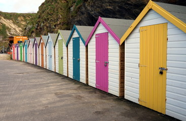 Row of colorful beach huts at the bottom of a rocky cliff on the sea shore