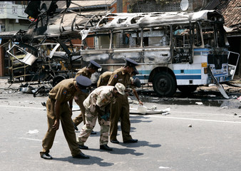 Police officers search for evidence near the wreckage of a bus after a bomb explosion in Colombo