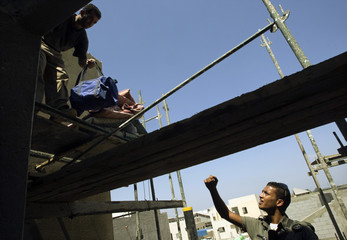 Palestinian labourer removes belongings from roof of house during operation to catch illegal workers at construction site in Givat Brenner