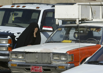 A woman grieves as she waits to claim the body of a relative who was killed in a bomb attack in Baghdad