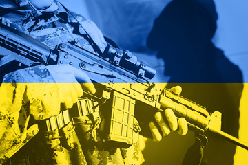 Soldier with machine gun with national flag of Ukraine