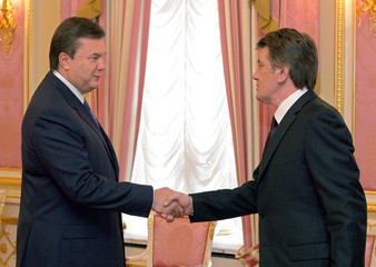 Ukraine's President Yushchenko shakes hands with his prime minister and adversary, Yanukovich, in Kiev