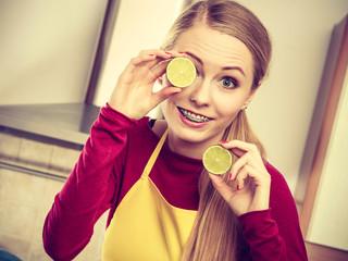 Woman holding fruit lemon half on eyes