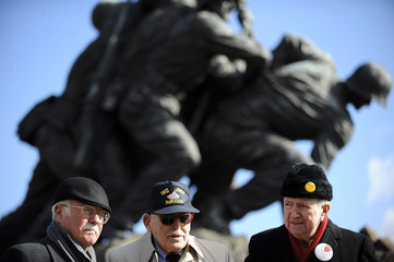Veterans stand together after a ceremony in honor the 64th anniversary of the raising of the US flag on the island of Iwo Jima during World War II, at the Marine Corps War Memorial in Arlington, Virginia