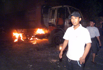 INDONESIAN MEN WALK PAST A TRUCK BURNED BY HUNDREDS OF PEDICAB DRIVERS IN JAKARTA.