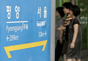 Passengers walk past a signboard at the Imjingang station in Paju