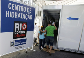 Woman walks with her daughter as she receives treatment after being diagnosed with dengue at hydration tent in Rio de Janeiro