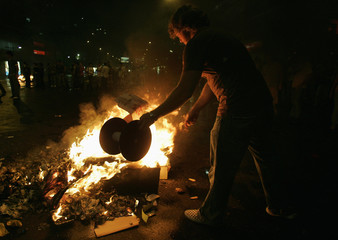 A man sets up a burning barricade during a protest after the channel RCTV was forced off the air in Caracas
