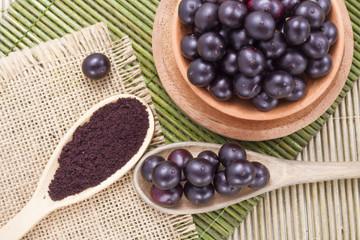 Fruits and acai powder originating from the Amazon on wood (Euterpe oleracea)