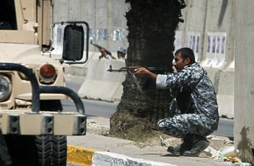 Iraqi policemen fire back as shots were fired at the main road used by Iraqi pilgrims on their way to attend a Shi'ite religious ritual in Baghdad
