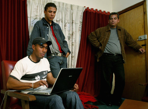 Cuban sport trainer Ciero reviews his laptop while Terry looks on after a Reuters interview in Bogota