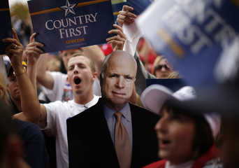 A suppporter holds a cardboard standee of U.S. Republican presidential nominee Sen. John McCain (R-AZ) as he speaks during a rally in Woodbridge, Virginia