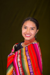 Beautiful hispanic model wearing andean traditional clothing smiling and posing for camera, dark yellow background