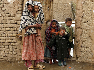 An Afghan family stand outside their house on a snowy day in Bamiyan province