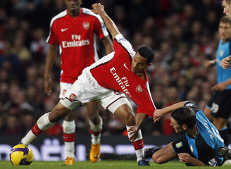 Arsenal's Walcott challenges Aston Villa's Barry during their English Premier League soccer match at the Emirates Stadium in London