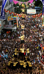 Indian devotees form human pyramid as they try to break clay pot containing butter during ...