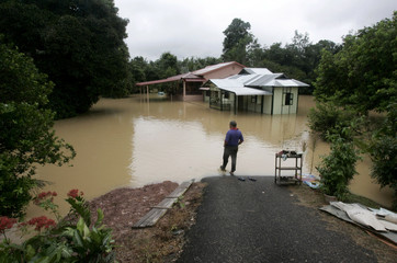 A villager looks at his flooded neighbourhood in Johor