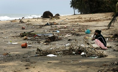 A woman weeps as she sits on the destroyed beach at Karaitivu, Sri Lanka.