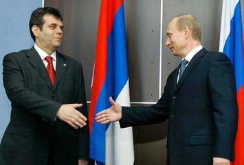 Russian President Putin and Serbian PM Kostunica shake hands during meeting in St.Petersburg
