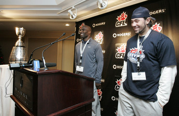 Winnipeg Blue Bombers slotback Milt Stegall and fullback Chris Cvetkovic speak before a team breakfast with the Grey Cup Trophy in the background in Toronto
