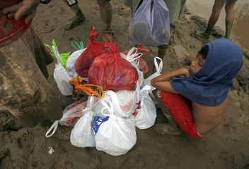 A boy waits for his parents with relief goods received after Typhoon Ketsana hit in Montalban Rizal