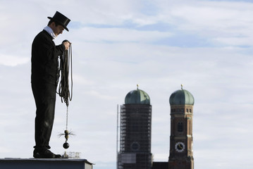 Chimney sweeper prepares to clean chimney at a roof of a house in Munich