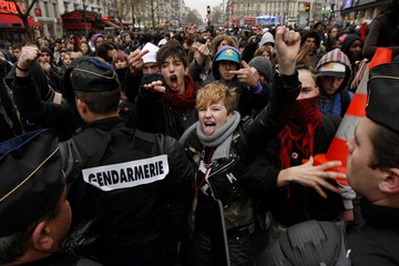 French high school students shout slogans as they face French gendarmes during a demonstration in Paris