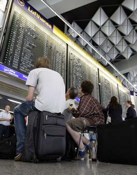Passengers wait in front of ticket desks of German airline Lufthansa in the departure hall of Frankfurt airport