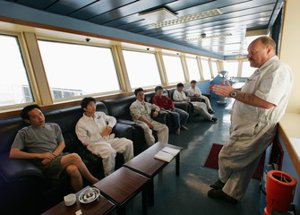 Production manager Malcolm Robertson (R) from Britain briefs Chinese crew members during a morning m..