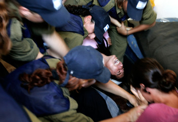 Israeli security forces remove a man out of his home at Shirat Hayam beach settlement in Gush Katif ...