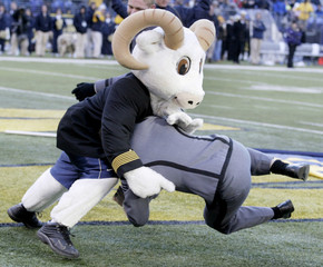 An Army cadet tackles the Navy mascot on the field after a Navy touchdown in Baltimore