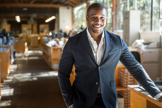 Handsome attractive african american modern professional smile standing confidently at the large interior workspace