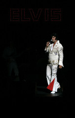 An Elvis Presley impersonator sings at the Palladium theatre in London