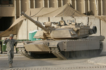 A U.S. soldier leads an M1 Abrams tank as it rolls into U.S. military Forward Operating base Loyalty in Baghdad