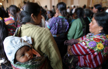 GUATEMALAN MAYA INDIANS WAIT FOR THE COMMENCEMENT OF A WAR REPARATIONS CEREMONY.