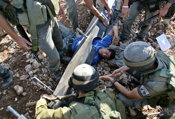 Israeli soldiers remove a Palestinian demonstrator chained to the ground during a protest against Is..