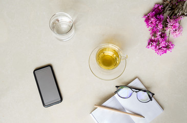 Top view cup of tea with flower , cell phone, glass of water and glasses with pencil