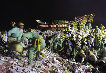 Volunteer temple workers prepare to burn Wang Ye's boat together with paper money offerings during Chinese traditional ceremony to drive away evil spirits in Pingtung county, Taiwan