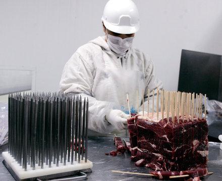 A butcher prepares sticks of meat at an abattoir in Brazil.