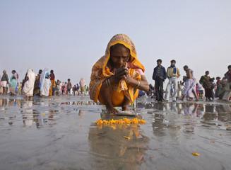 A Hindu pilgrim worships on the banks of River Ganges at Sagar Island, south of Kolkata