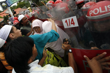 Riot police scuffle with protesters during demonstration on the road to palace where swearing-in ceremony for new Perak state chief minister will be held in Kuala Kangsar
