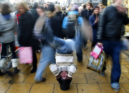 A man, performing a head stand on a bucket for money from passers by, falls forward in Princes Street in Edinburgh