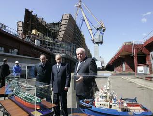 Incoming Prime Minister Vladimir Putin listens to general director of Somcomflot Sergey Frank and director of Admiralteiiskiye Shipyards Vladimir Alexandrov during his visit to St.Petersburg