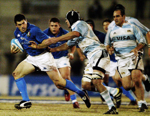 Italy's Masi tries to evade Argentina's Bouza and Ledesma during a rugby test match in Cordoba.
