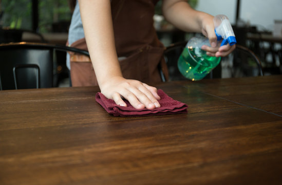 Waitress cleaning the table with spray disinfectant