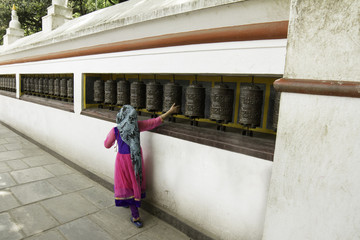 Nepali girl and prayer wheels.
