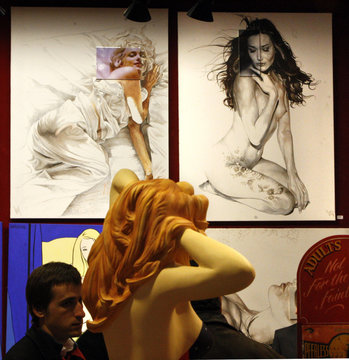Drawings of France's first lady Carla Bruni-Sarkozy (R) and U.S. actress Monroe by French artist Toutain are being put up for auction at Drouot auction house in Paris