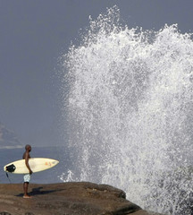 A surfer watches waves from Mirante point as heavy surf pounds a section of Arpoador beach in Rio de Janeiro